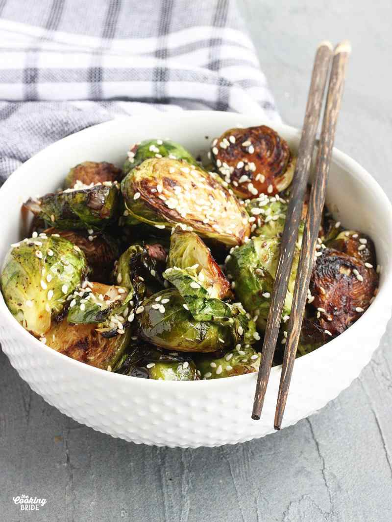 Stir fried Brussels sprouts garnished with sesame seeds in a white bowl with wooden chopsticks resting on the side of the bowl.