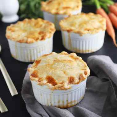 baked mini chicken pot pies on a black background with one bunch of carrots in the background and spoons resting on the side