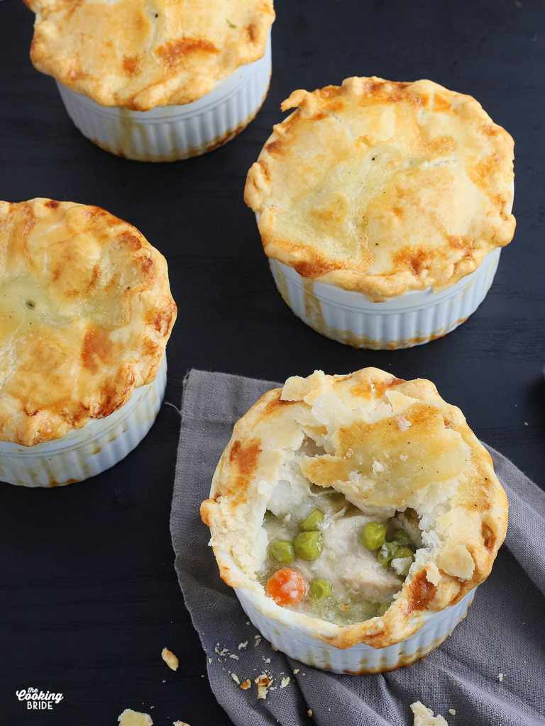 a mini chicken pot pie with a spoonful removed to show the filling