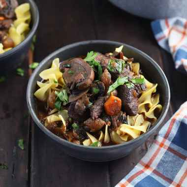 Venison bourguignon over egg noodles garnished with chopped parsley