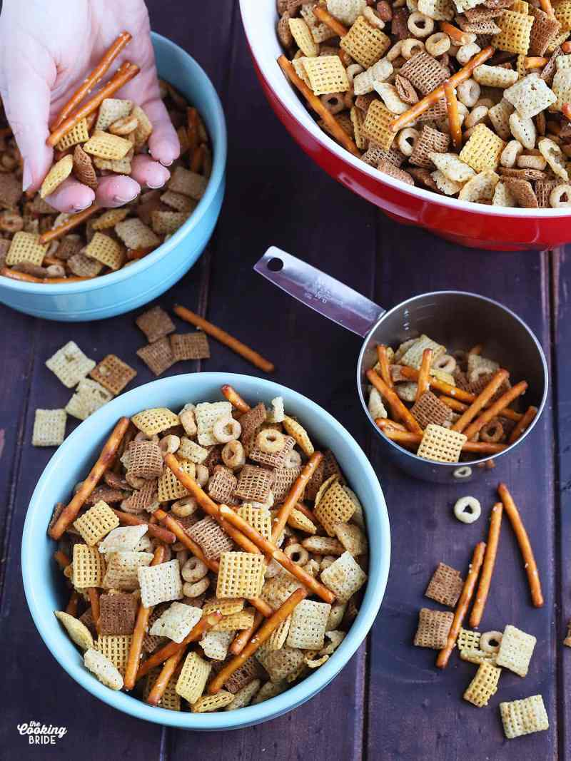 blue ceramic bowl full of chex mix with a metal measuring cup, red serving bowl full of chex mix to the side