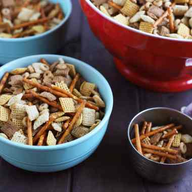 blue bowl full of chex mix with metal measuring cup to the side