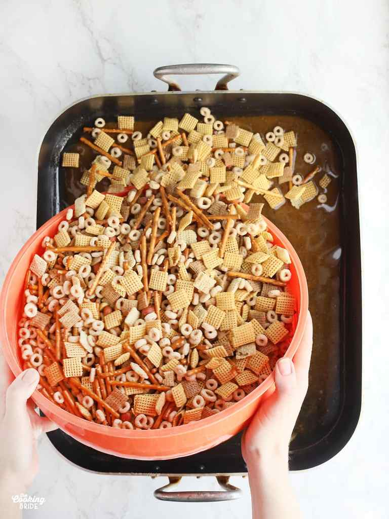 hand pouring an orange bowl of mixed chex mix ingredients into a roasting pan of melted butter and Worcestershire sauce