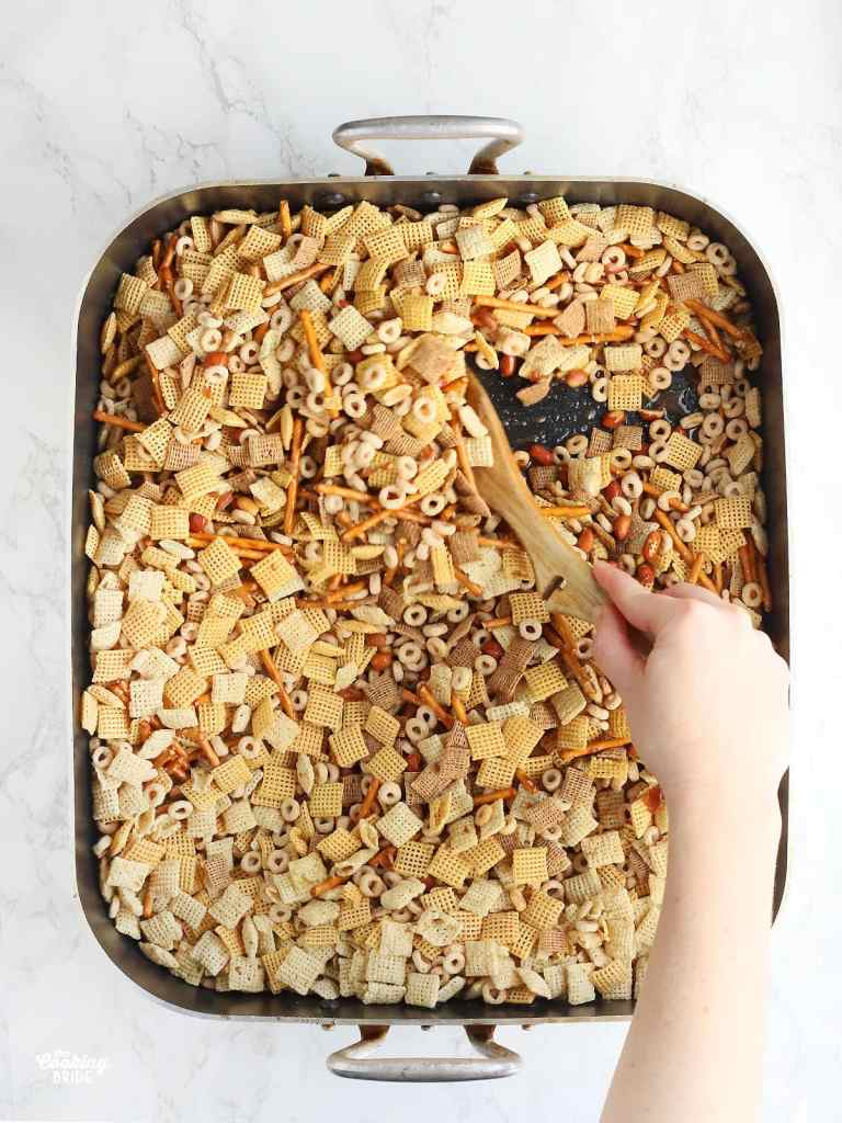 hand using a wooden spoon to stir Chex mix in a large roasting pan