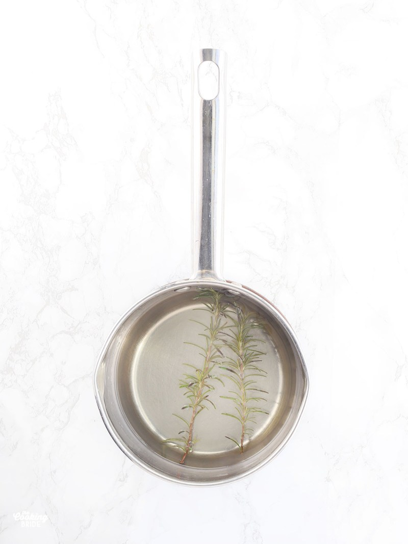 two sprigs of rosemary floating in a pan of simple syrup