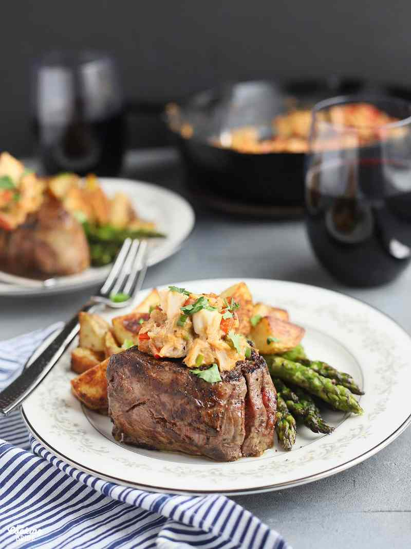 filet on a China plate topped with crabmeat and garnished with parsley, fork the the side and glasses of red wine in the background
