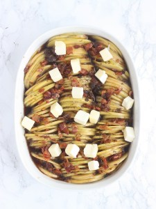 sliced potatoes and bacon in a white casserole dish dotted with butter right before baking