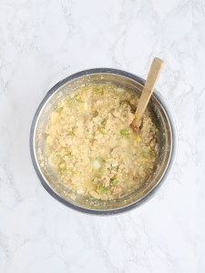 mixing cornbread dressing ingredients in a stainless steel mixing bowl