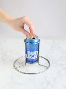 hand dropping a clove of garlic into a can of beer in a chicken roaster