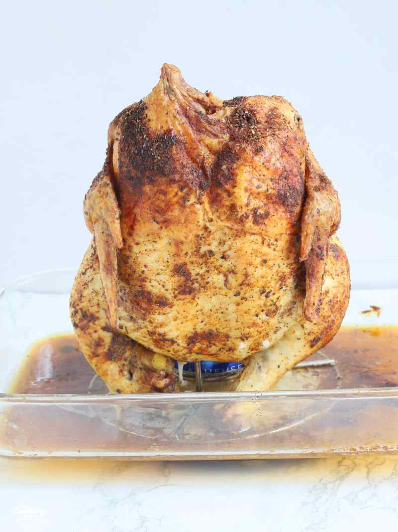 roasted beer can chicken sitting on a roaster in a glass casserole dish