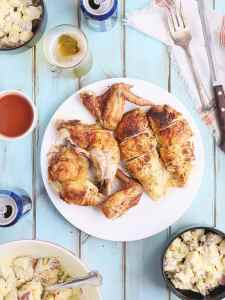 overhead shot of carved beer can chicken on a white plate with bowls of potato salad, cold beer and sauce on the side