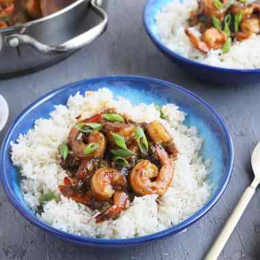 cooked Cajun shrimp laying on a bed of rice garnished with green onions in a blue bowl.