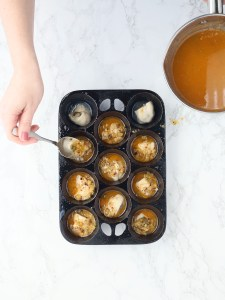 hand spooning garlic butter sauce over the top of each oyster in a muffin pan