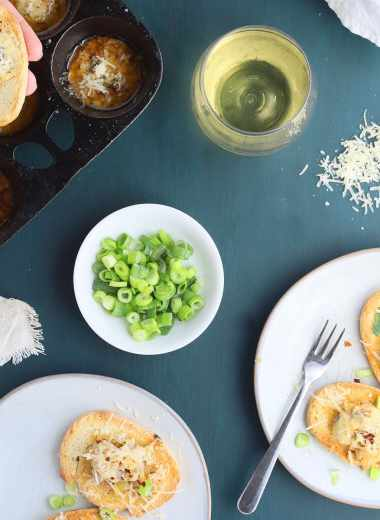 two gray plates with oysters on toast sprinkled with Parmesan cheese, sliced green onions, glasses of white wine, a hand spooning an oyster onto a piece of bread