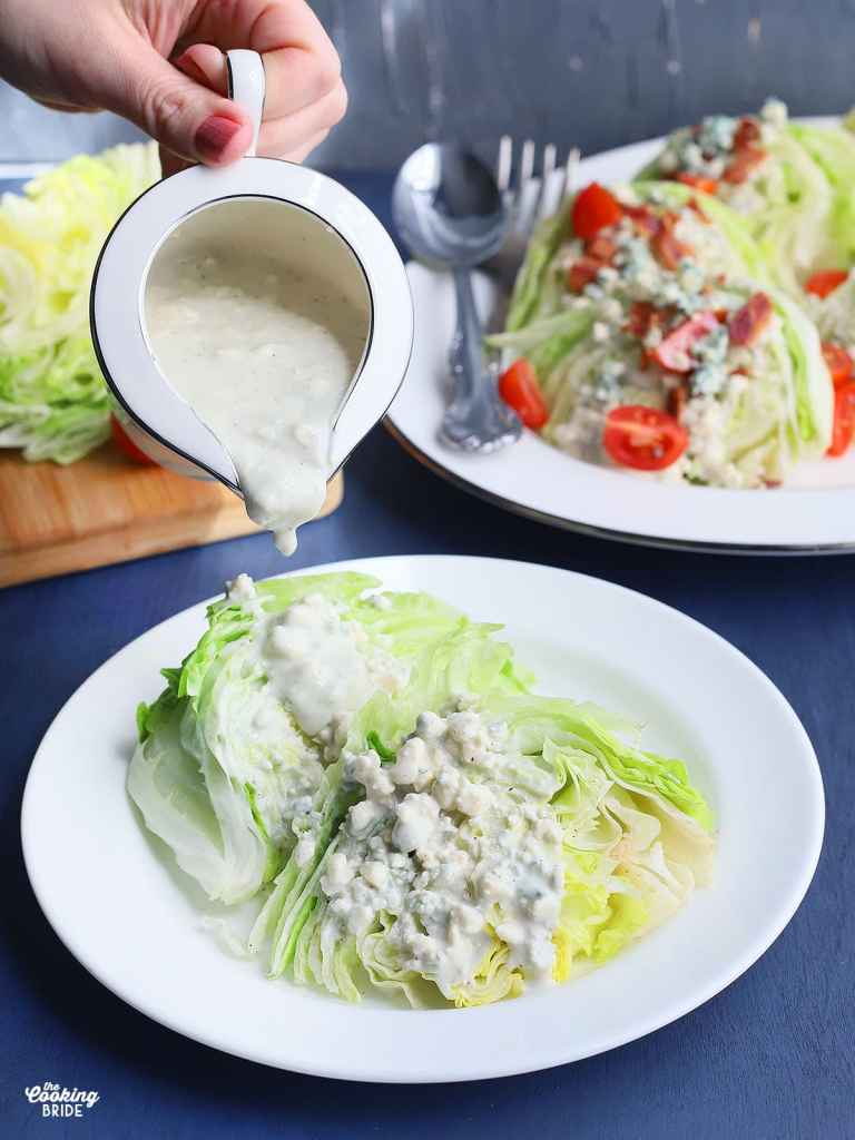 hand pouring blue cheese dressing over a lettuce wedge on a white plate