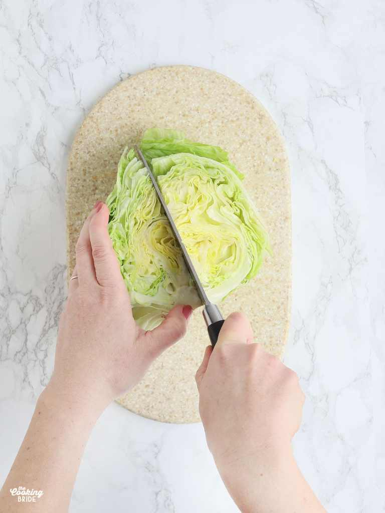 pair of hands using a sharp knife to cut a head of iceberg lettuce into quarters
