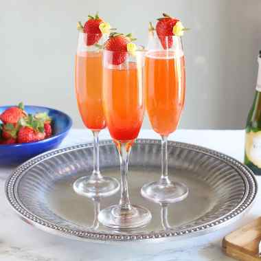 three strawberry champagne cocktails sitting on a silver tray