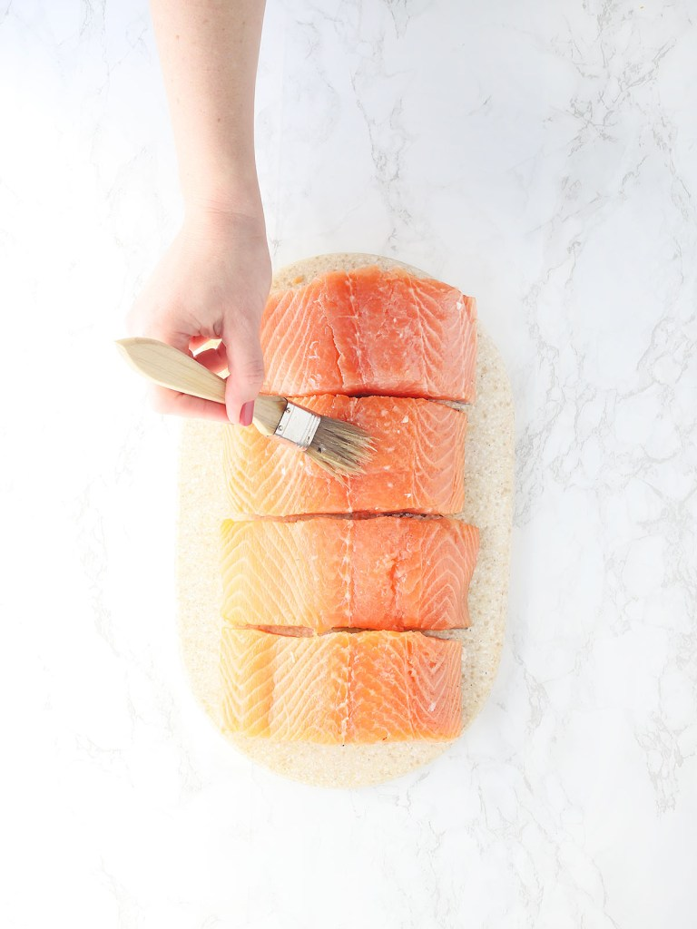 hand brushing four salmon fillets with olive oil