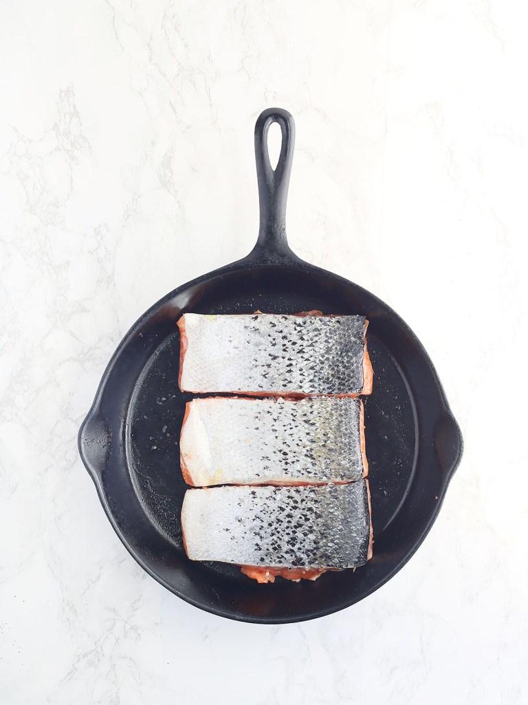 salmon filets skin side down in a cast iron skillet