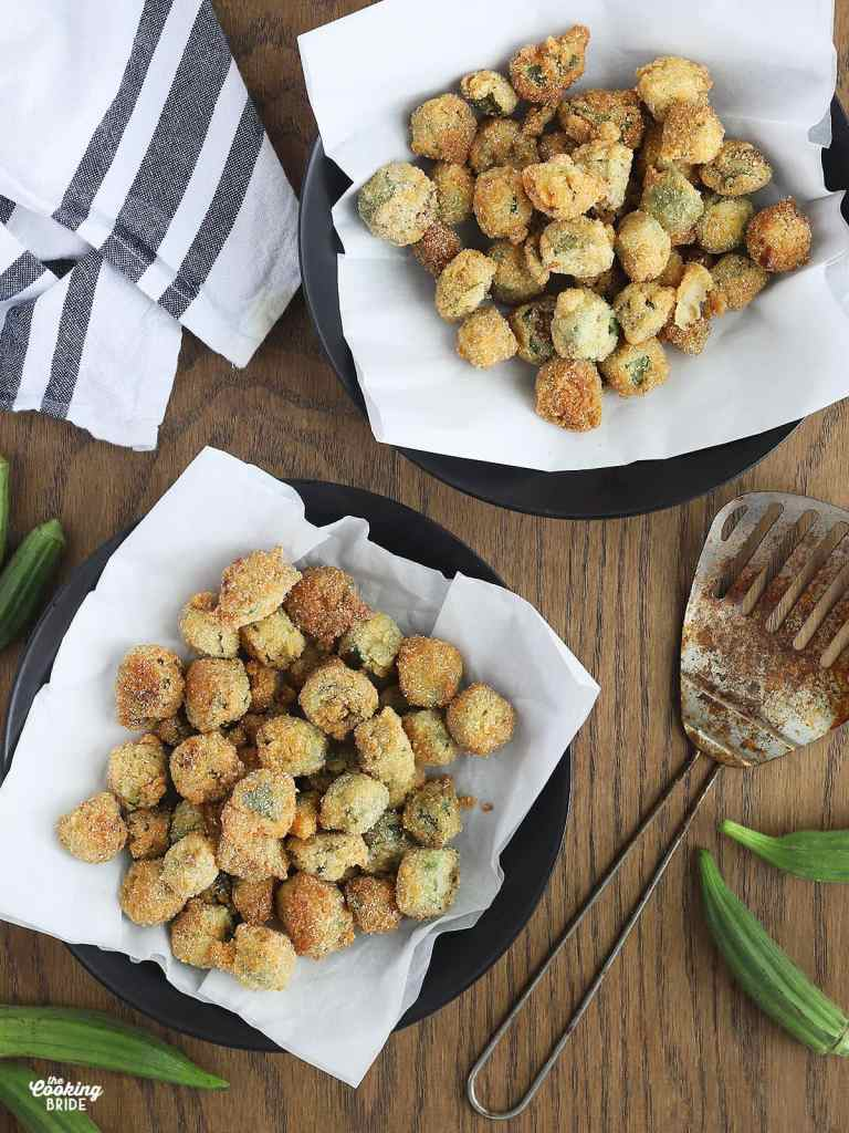overhead shot of two black dishes filled with fried okra, a black and white napkin, metal strainer and whole okra to the side