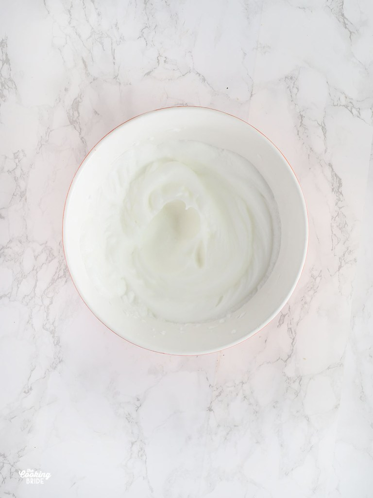 egg whites with stiff peaks in a mixing bowl