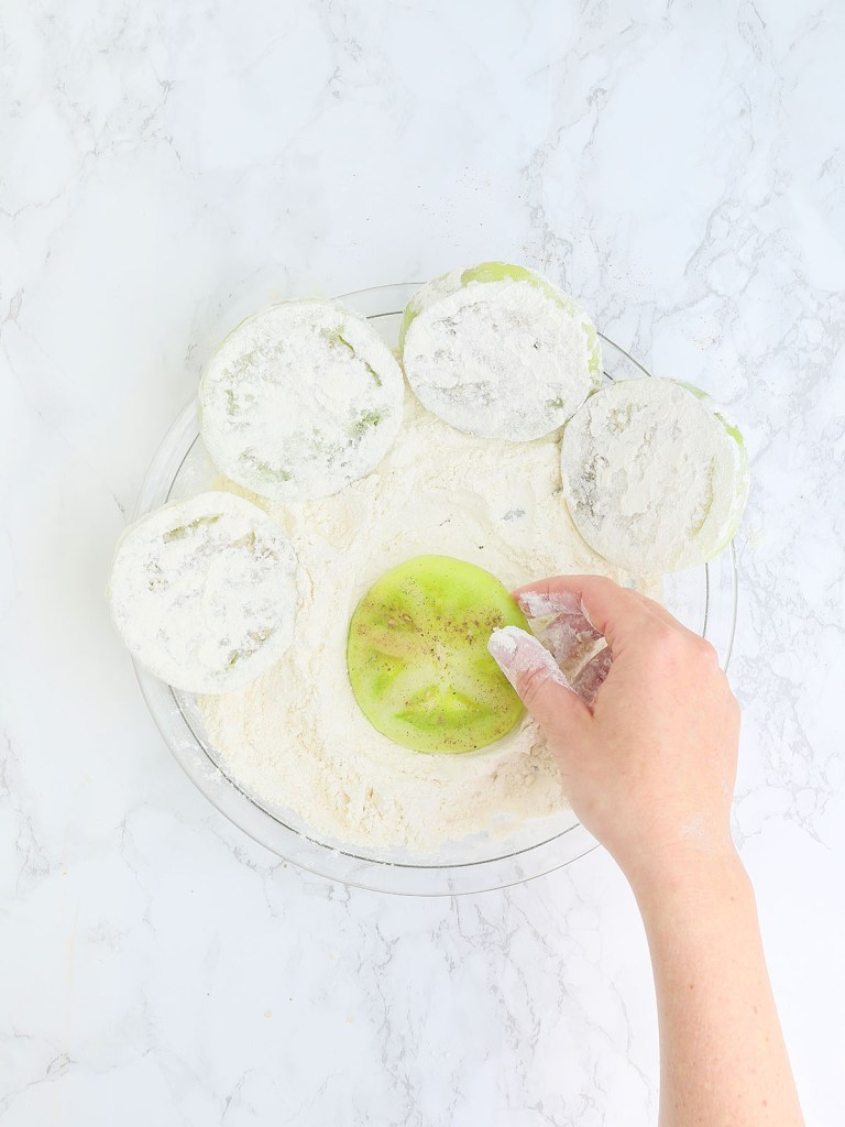 hand coating a sliced green tomato in flour