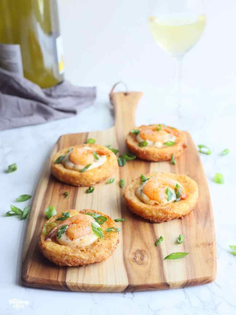 four shrimp on fried grit cakes arranged on a wooden cutting board