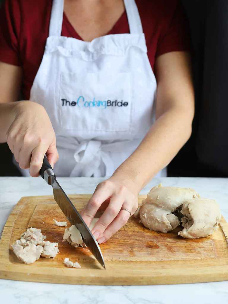 figure cutting into cooked chicken thighs on a wooden cutting board