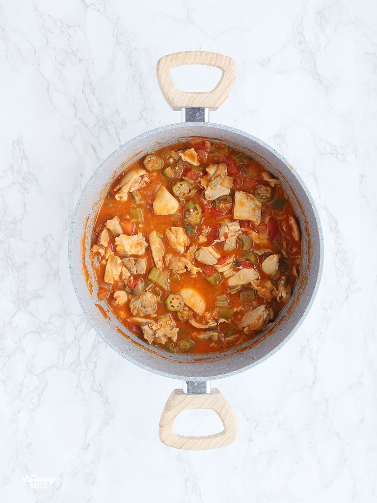 overhead shot of a gray pot of chicken peanut stew on a white marble background