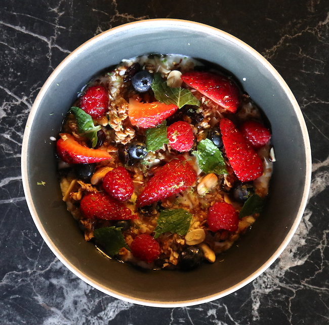 A bowl with yogourt, strawberries, mint, blueberries and granola