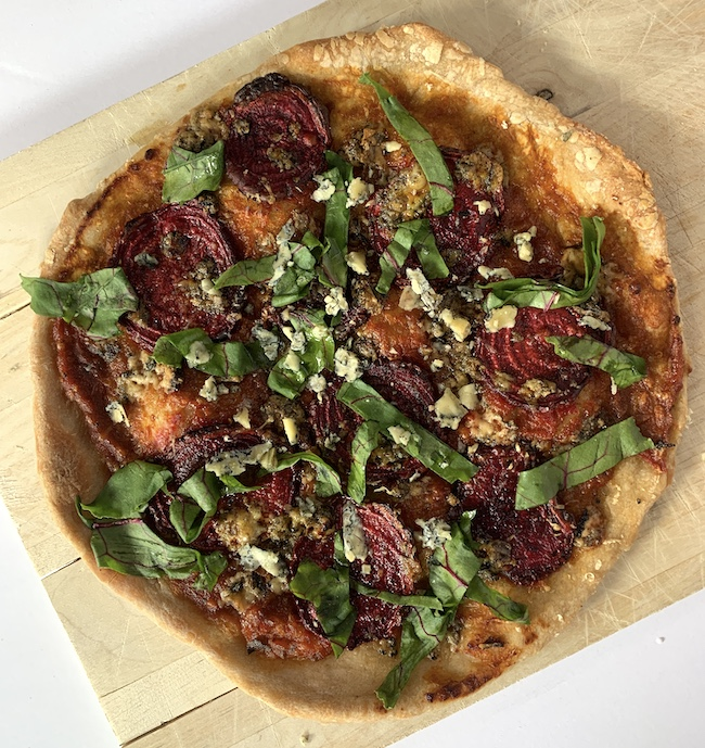 a pizza topped with beet slices, blue cheese and greens