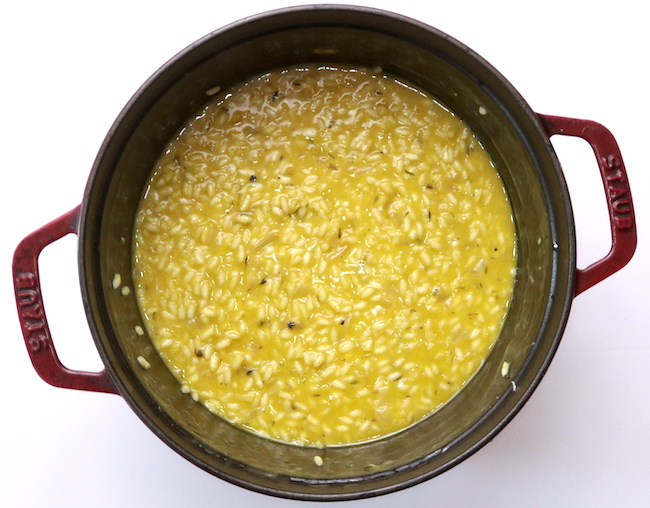 A large pot filled with golden squash risotto