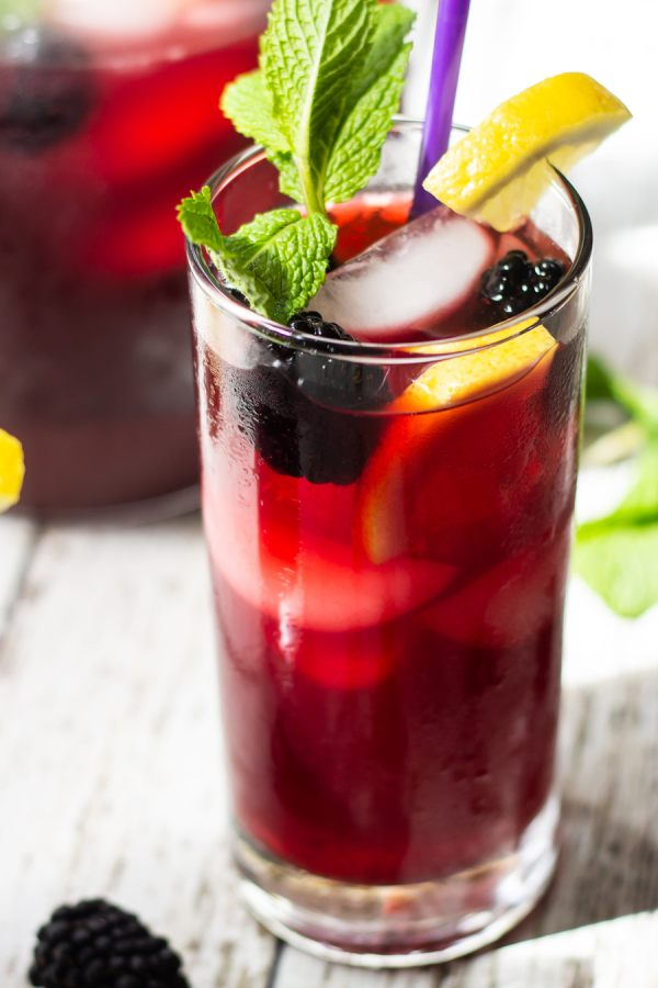 blackberry iced tea with whole blackberries in glass