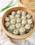 Chinese pearl meatballs covered in glutinous rice in a bamboo steamer.