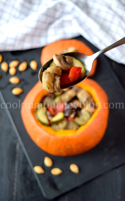 Stuffed pumpkin with baked vegetables is beautiful and healthy meal. Spoon with baked vegetables