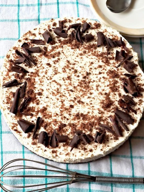 Baileys cheesecake slice on a plate, decorated with chocolate. With serving plates aside.