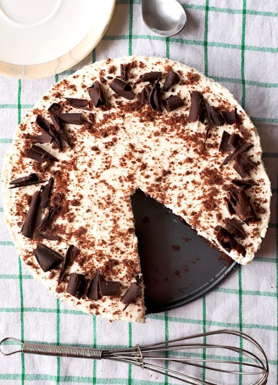 Baileys cheesecake slice on a plate, decorated with chocolate, one slice missing