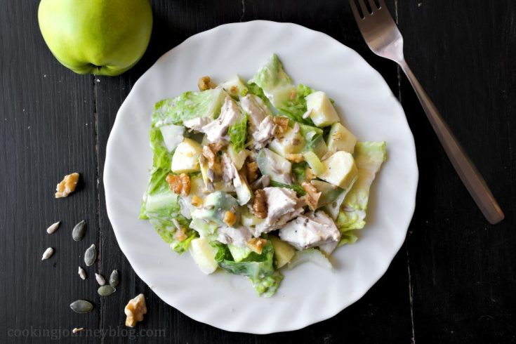 Avocado chicken salad, apples on the background