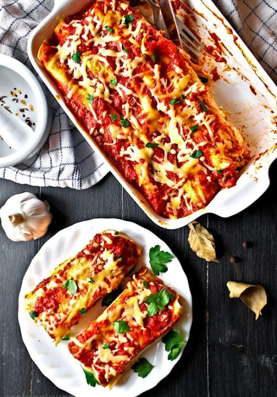 Chicken enchilada bake with red enchilada sauce on the black table