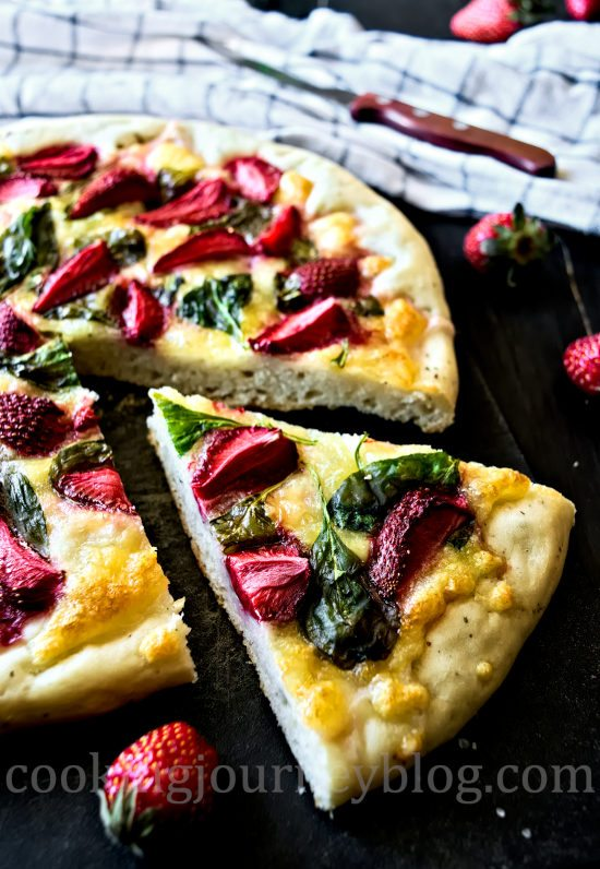 Mozzarella strawberry pizza, one slice on a black table