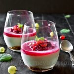 gooseberry fool served in two glasses on a black table with fresh gooseberries, spoon and mint leaves