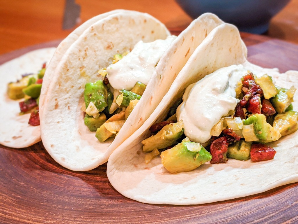 Spicy Chorizo and avocado tacos with onion and lime crema
