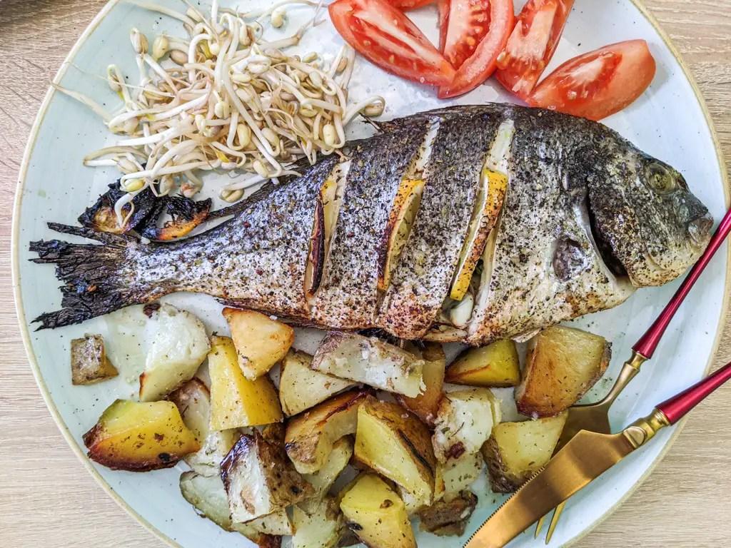 Mediterranean Baked Sea Bream (Gilt Head Bream, Dorada, Orata). Served with roast potatoes, fresh tomatoes, and bean sprouts