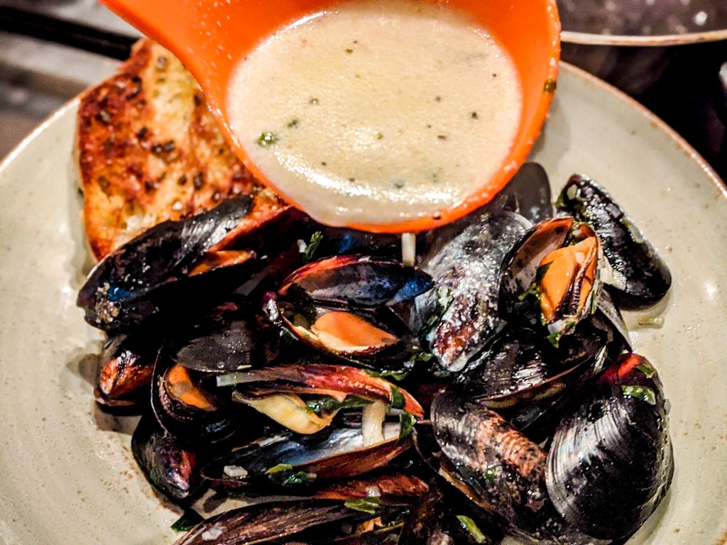 Mussels with roquefort sauce being poured over