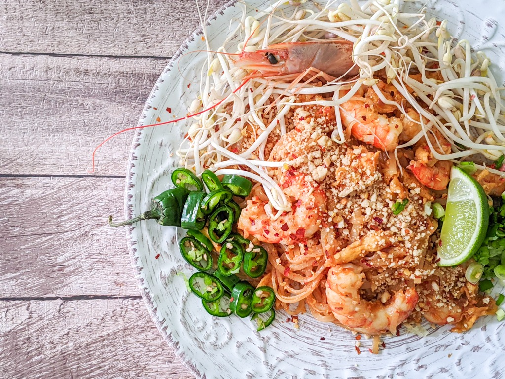 homemade prawn shrimp pad thai with chilies, limes, bean sprouts and more