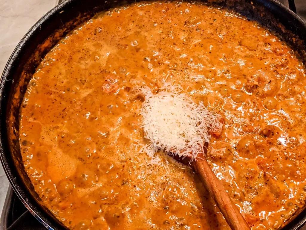 adding cheese to the shashlik pasta sauce