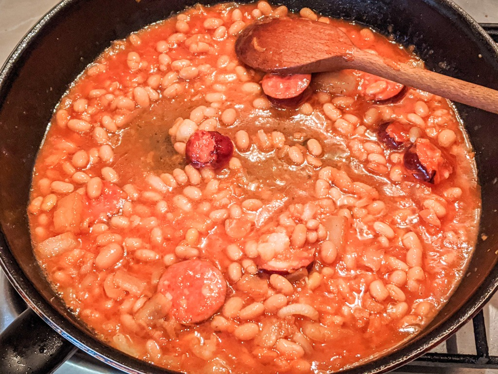 simmering the beans and sausage slices in salo (ukrainian pork fat)