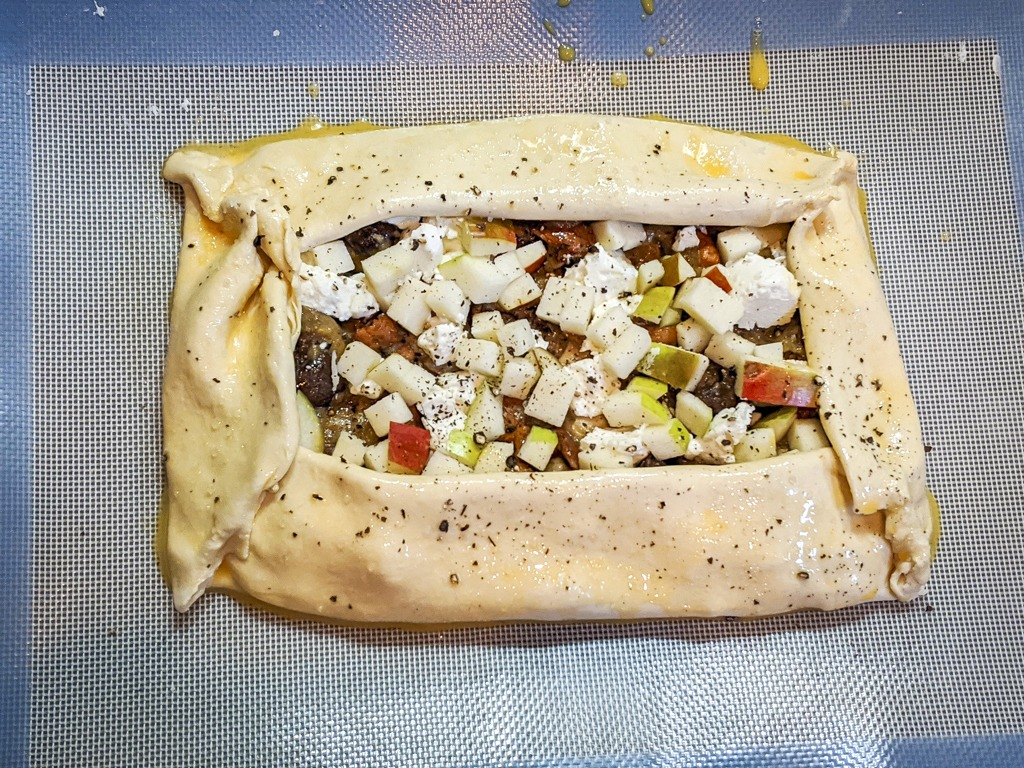 Unbaked Wild Mushroom And Goat Cheese Galette on a silicone baking mat