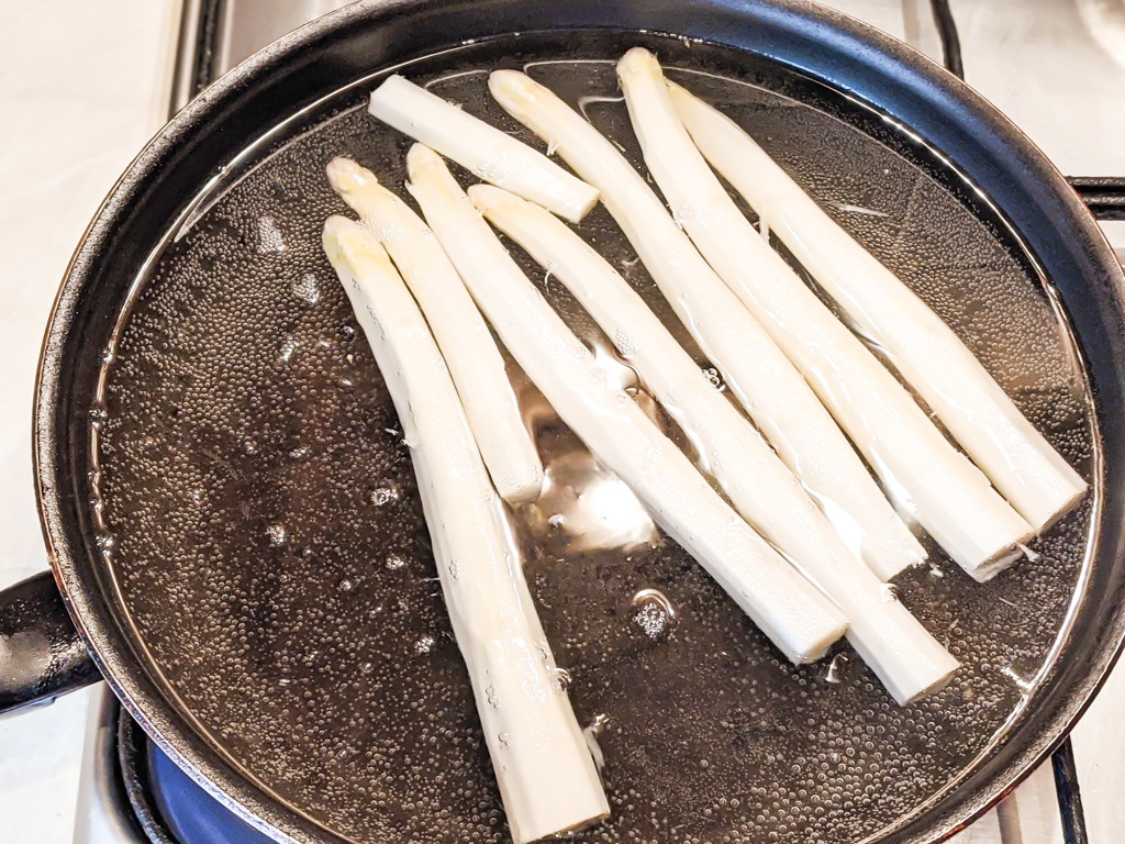 boiling the white asparagus in a water and butter bath