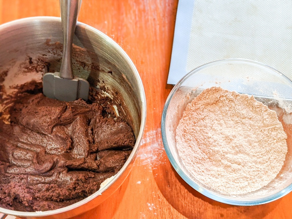 Mexican Hot Chocolate Cookies dough and a bowl of powdered sugar and cinnamon for rolling